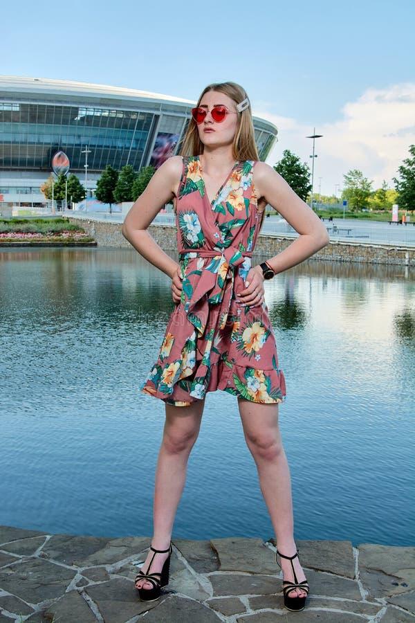 Jeune femme attirante Lunettes de soleil rouges, robe de couleur Portrait du ` s de fille Fond de stade de football photo libre de droits