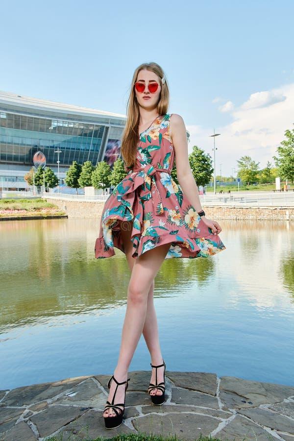 Jeune femme attirante Lunettes de soleil rouges, robe de couleur Portrait du ` s de fille Fond de stade de football image stock
