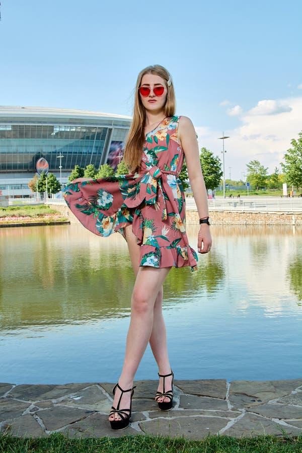 Jeune femme attirante Lunettes de soleil rouges, robe de couleur Portrait du ` s de fille Fond de stade de football images stock