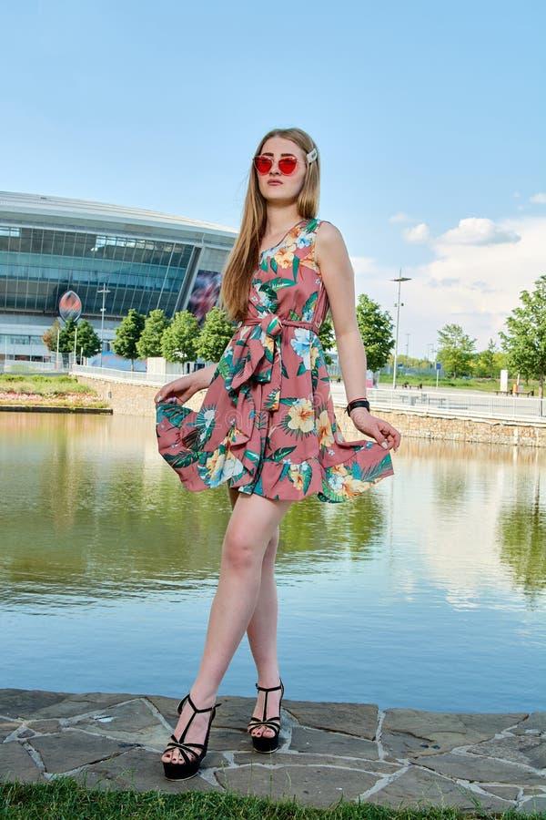 Jeune femme attirante Lunettes de soleil rouges, robe de couleur Portrait du ` s de fille Fond de stade de football photo stock