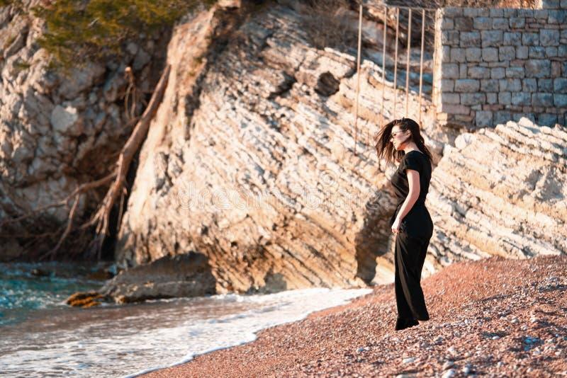 Jeune femme attirante marchant sur une plage ensoleill?e au rivage Voyageur et blogger photos stock