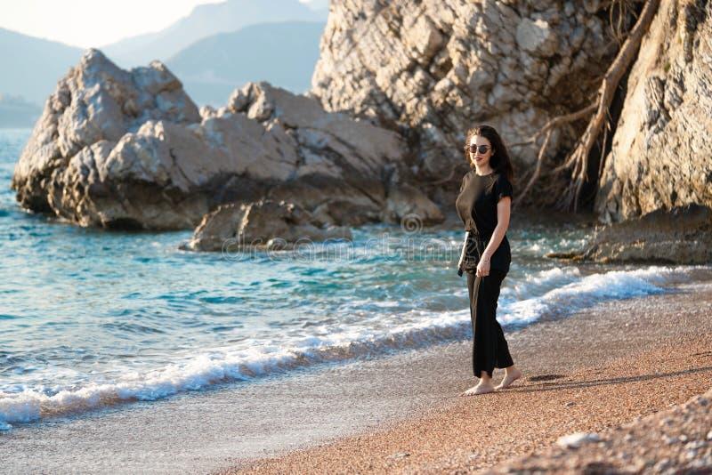 Jeune femme attirante marchant sur une plage ensoleill?e au rivage Voyageur et blogger photographie stock
