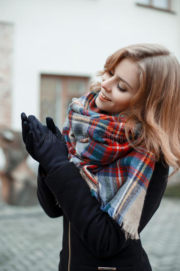 Jeune femme attirante merveilleuse dans un manteau noir élégant avec une écharpe chaude de laine dans des poses noires de gants l photo libre de droits