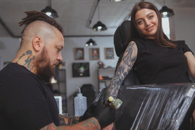 Jeune femme attirante obtenant le nouveau tatouage par le tatoueur professionnel images stock