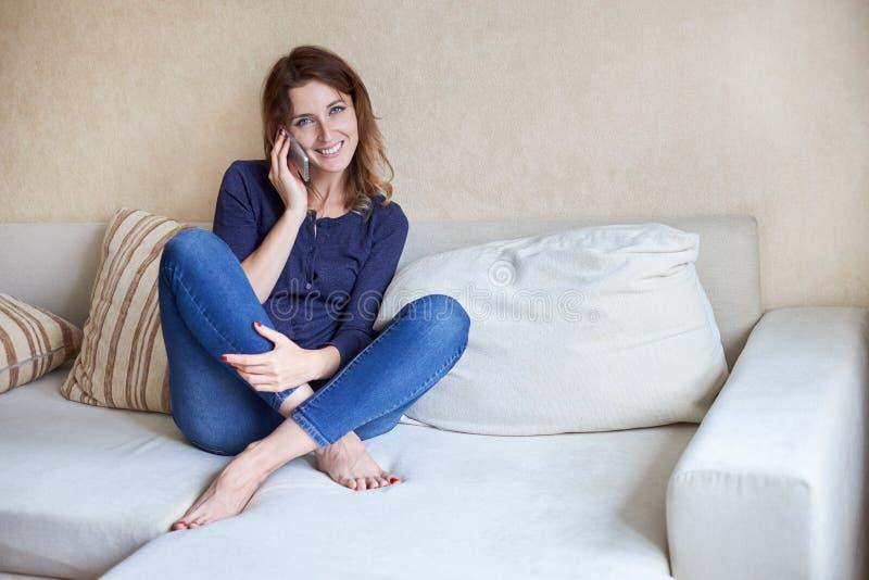 Jeune femme attirante parlant au téléphone portable et souriant à la maison photographie stock libre de droits