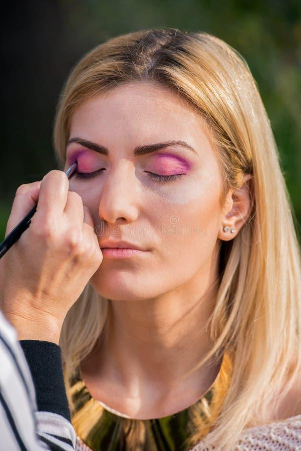 Jeune femme attirante pendant une session de maquillage photo stock