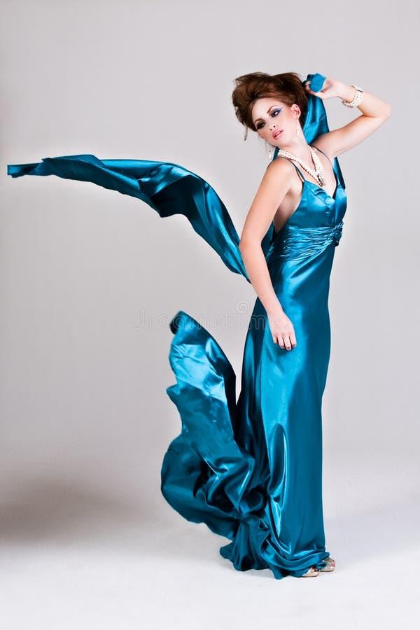 Jeune femme attirante portant une robe bleue de satin image libre de droits