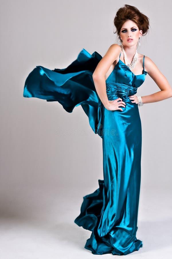 Jeune femme attirante portant une robe bleue de satin photos stock