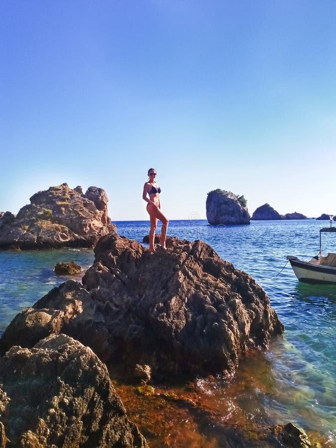 Jeune femme attirante posant dans un maillot de bain noir sur la falaise de l'île tropicale avec le bateau près photos libres de droits