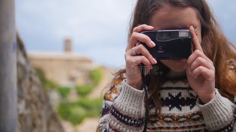 Jeune femme attirante prendre une photo de quelque chose avec une vieille caméra photo stock