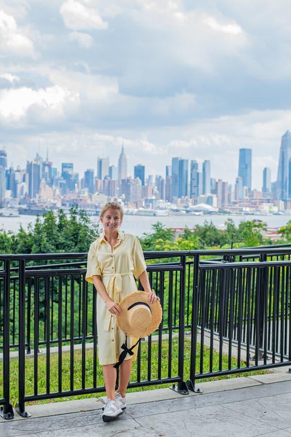 Jeune femme attirante regardant à la caméra et souriant sur le fond de New York City photos libres de droits