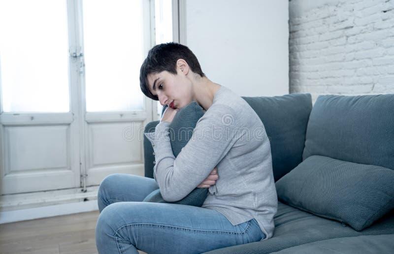 Jeune femme attirante regardant en bas de accabler triste et seule sur le divan ? la maison photos libres de droits