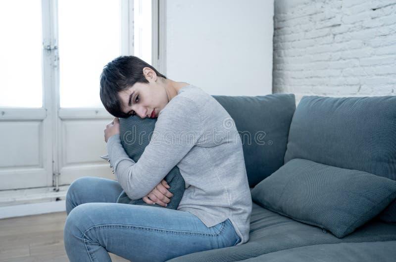 Jeune femme attirante regardant en bas de accabler triste et seule sur le divan ? la maison images libres de droits