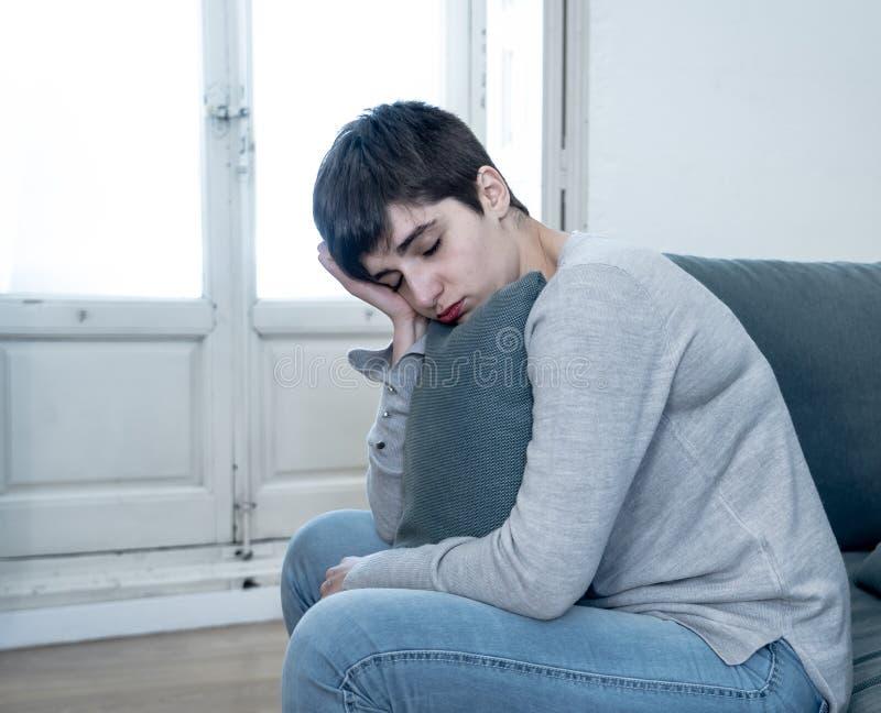 Jeune femme attirante regardant en bas de accabler triste et seule sur le divan ? la maison photographie stock