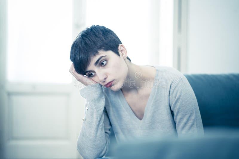 Jeune femme attirante regardant en bas de accabler triste et seule sur le divan ? la maison images stock