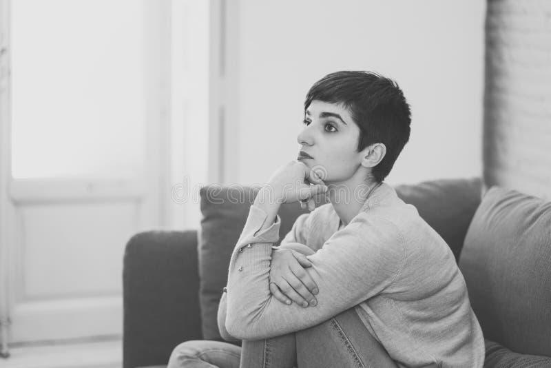 Jeune femme attirante regardant en bas de accabler triste et seule sur le divan ? la maison photos stock