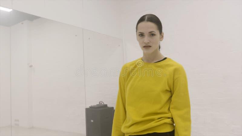 Jeune femme attirante regardant la caméra et posant dans la chambre blanche avec le miroir action Regard sérieux simple de jeune photos libres de droits