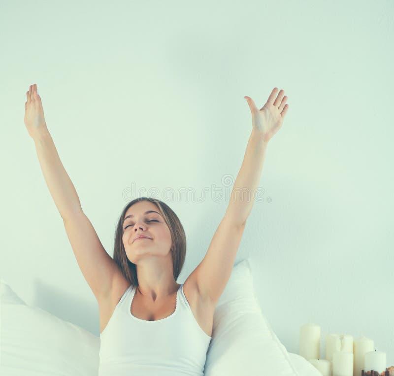 Jeune femme attirante s'étirant dans le lit après s'être réveillé photo stock