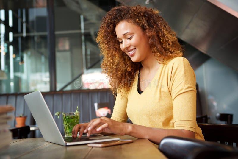 Jeune femme attirante s'asseyant au café et travaillant avec l'ordinateur portable photos stock