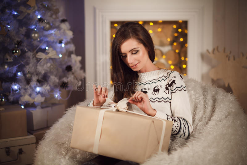Jeune femme attirante s'asseyant près de l'arbre de Noël et du g s'ouvrant image stock
