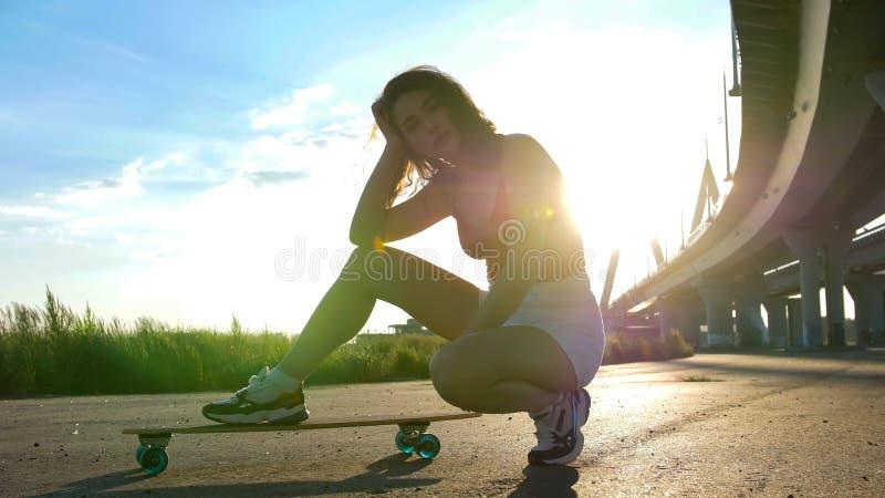 Jeune femme attirante s'asseyant sur la planche à roulettes sous le pont - lumière du soleil lumineuse photographie stock