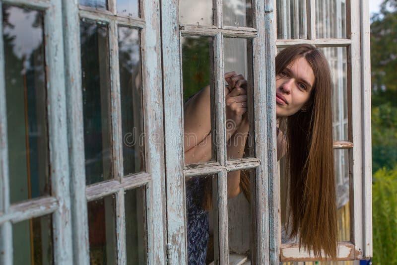 Jeune femme attirante s'asseyant sur un rebord de fenêtre dans la maison de campagne photo libre de droits