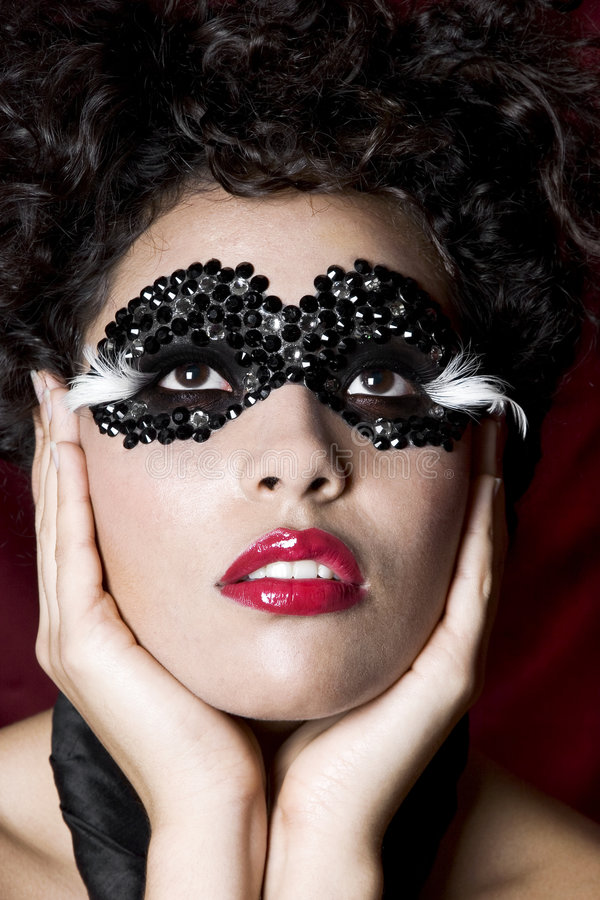 Jeune femme attirante s'usant un masque noir de gemme photographie stock