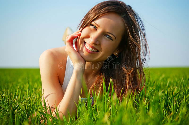 Jeune femme attirante se situant dans l'herbe verte photos stock