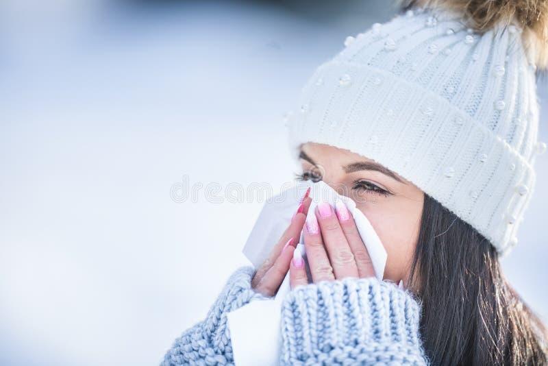 Jeune femme attirante soufflant son nez avec un tissu en hiver images stock