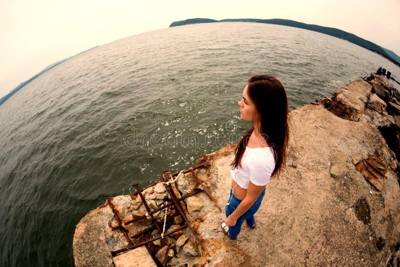 Jeune femme attirante sur la vieille jetée la mer image stock