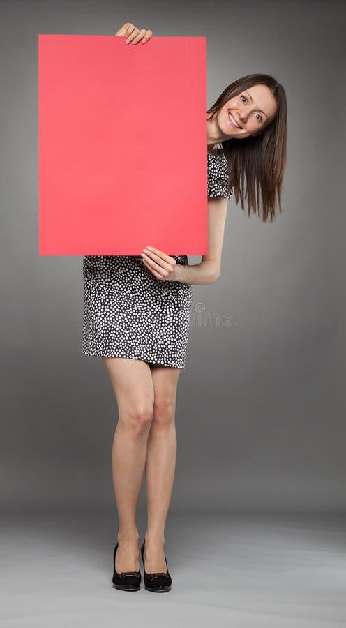 Jeune femme attirante tenant l'affiche rouge images libres de droits