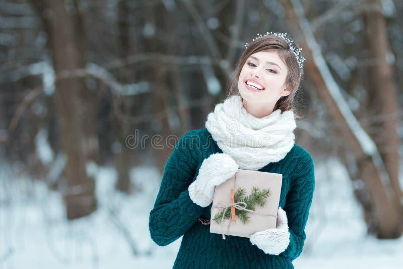 Jeune femme attirante tenant le cadeau de Noël photographie stock libre de droits