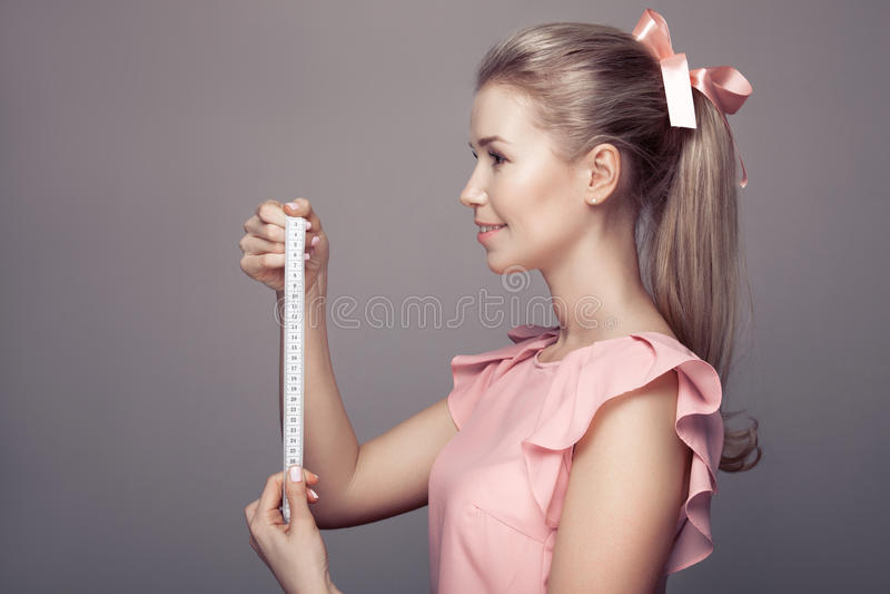 Jeune femme attirante tenant le ruban métrique photographie stock libre de droits