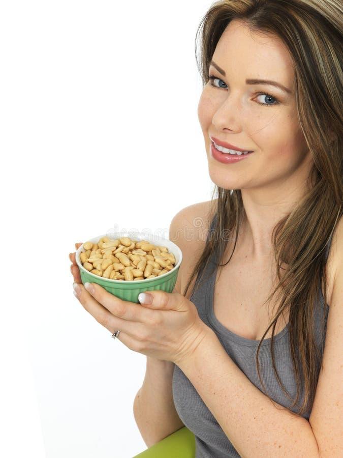 Jeune femme attirante tenant un bol d'arachides salées images stock
