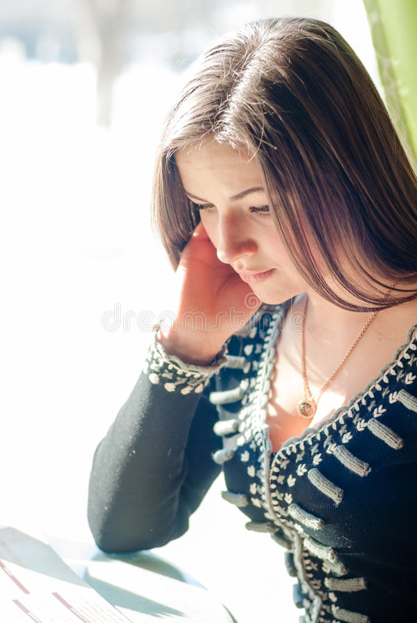 Jeune femme attirante tendre de brune s'asseyant dans un restaurant ou un café avec un livre de menu photographie stock