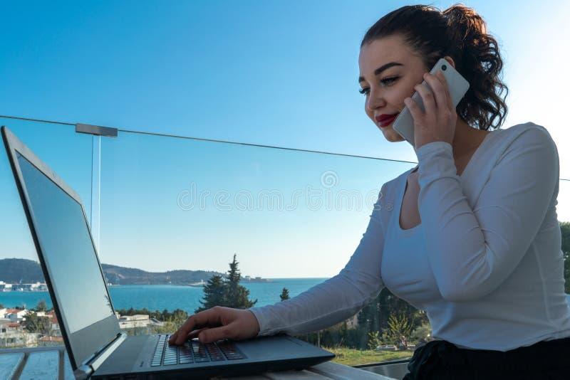 Jeune femme attirante travaillant sur l'ordinateur portable sur le balcon et appr?ciant la belle vue images stock