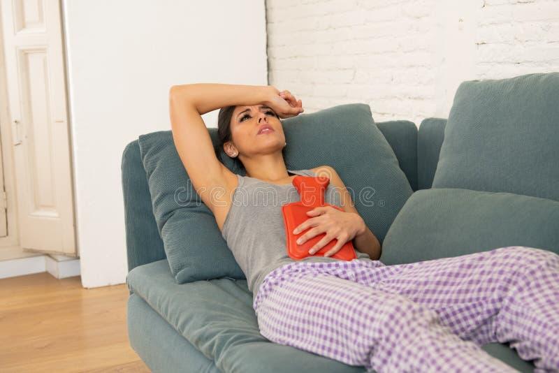 Jeune femme attirante triste ayant le mal de ventre douloureux de la douleur de période et des crampes menstruelles photo stock