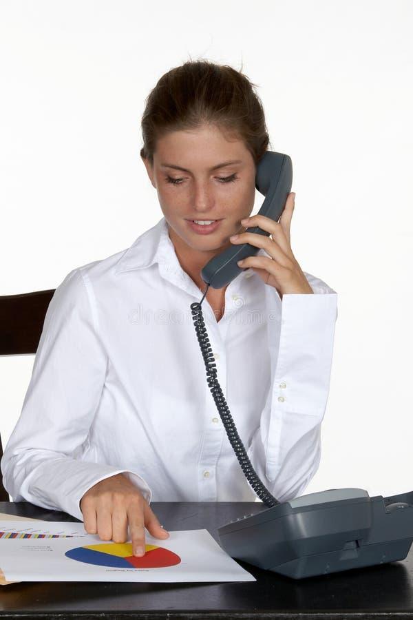 Jeune femme au bureau parlant au téléphone photographie stock