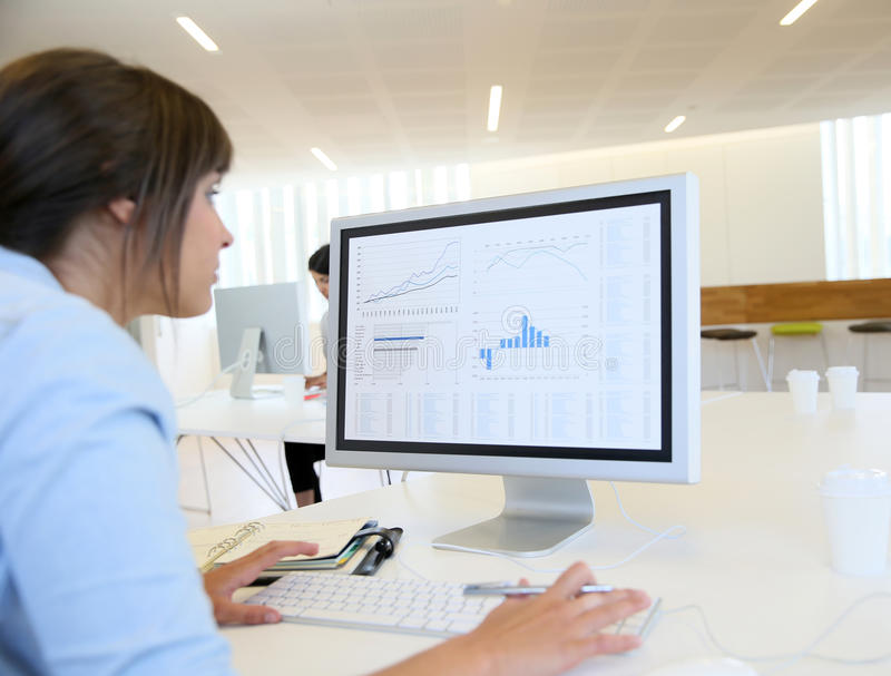 Jeune femme au bureau travaillant sur l'ordinateur photos libres de droits