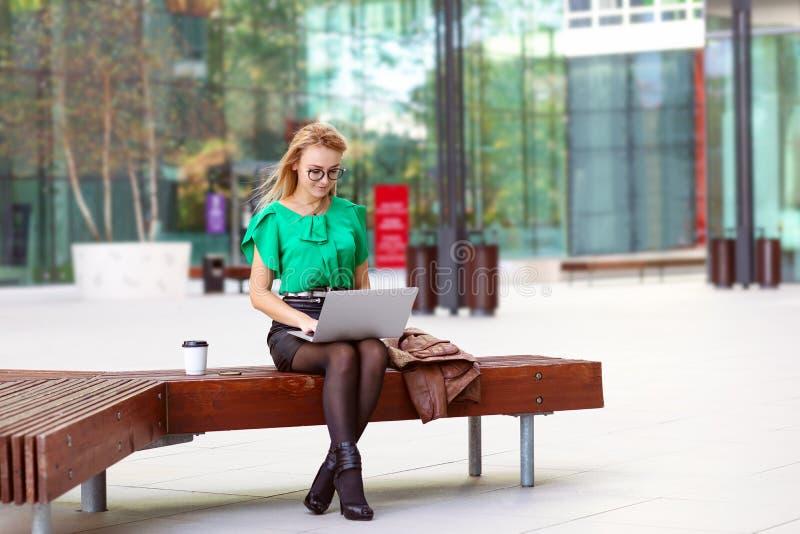 Jeune femme au-dessus d'une pause-café utilisant l'ordinateur portable en dehors des immeubles de bureaux modernes photo libre de droits