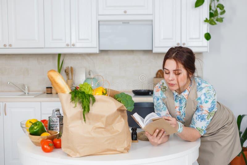 Jeune femme au foyer avec le livre de recettes photos libres de droits