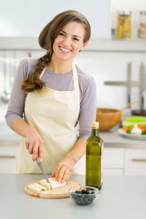 Jeune femme au foyer de sourire coupant le fromage frais images libres de droits