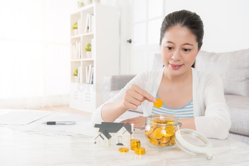 Jeune femme au foyer employant la pièce d'or d'économie de boîte de dépôt images libres de droits
