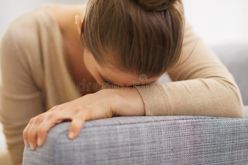 Jeune femme au foyer frustrante s'asseyant sur le sofa photographie stock libre de droits