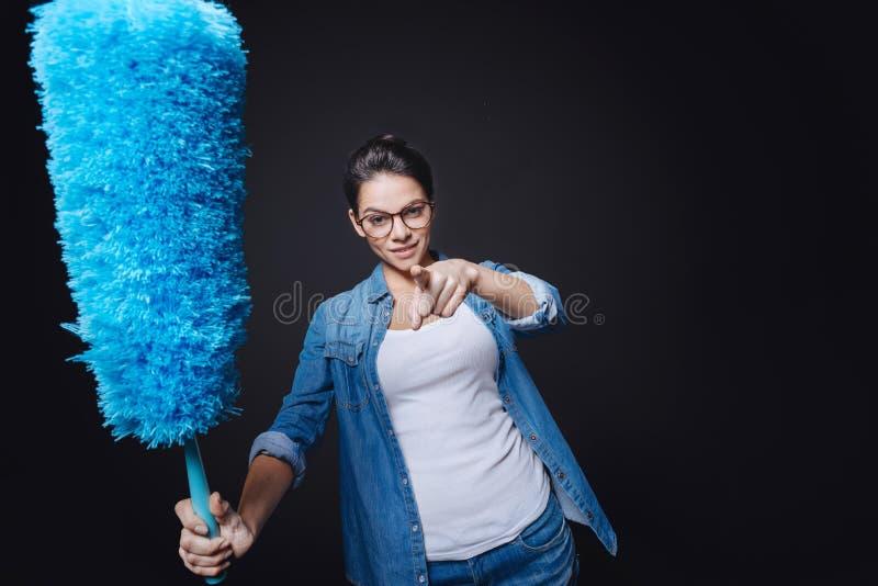 Jeune femme au foyer résolue tenant la brosse de saupoudrage image stock