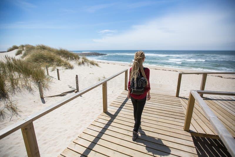 Jeune femme aux épouvantails debout près du rivage océanique image libre de droits