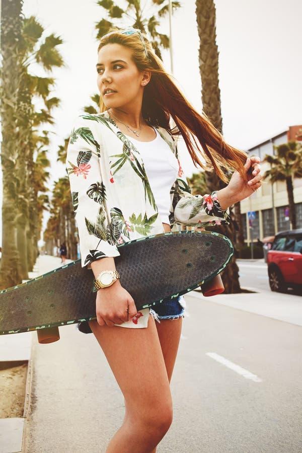 Jeune femme aux cheveux longs à la mode posant avec son longboard appréciant le beau jour en été photographie stock libre de droits