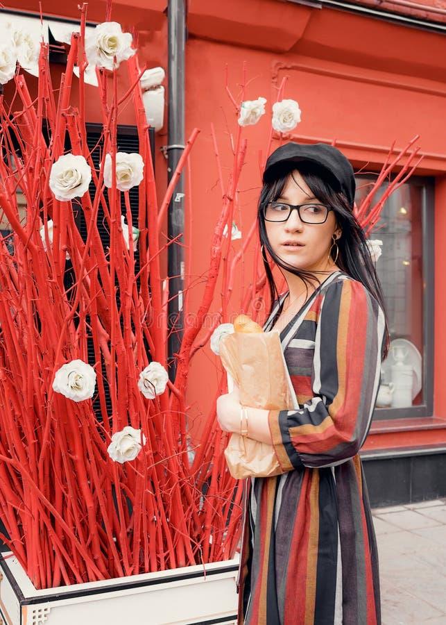 Jeune femme aux cheveux longs de brune dans une robe et un chapeau lumineux contre un mur rouge photo libre de droits