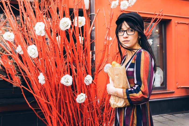 Jeune femme aux cheveux longs de brune dans une robe lumineuse contre un mur rouge photo libre de droits