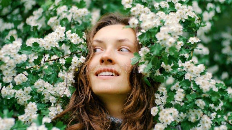 Jeune femme aux yeux verts de sourire heureuse avec des fleurs Beauté normale photo stock